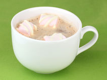 Cup of cappucino with marshmallows. On green background royalty free stock photos