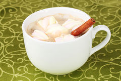 Cup of cappucino with marshmallows. And cinnamon on green tablecloth stock photography
