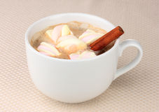 Cup of cappucino with marshmallows. And cinnamon on beige background royalty free stock image