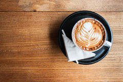 A cup of cappucino and a napkin on a wood Royalty Free Stock Photos