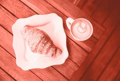Cup of capuccino and croissant on table, colored in Living Coral tone royalty free stock photos
