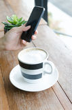 Cup of capuccino and smart phone Royalty Free Stock Photo