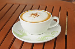 A cup of Capuchino coffee on wooden background. Royalty Free Stock Images