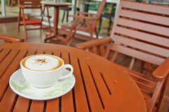 A cup of Capuchino coffee on wooden table Stock Photography