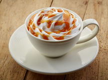 Cup of caramel cappuccino coffee. On wooden table Stock Photography
