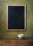 Cup and chalk board Stock Images