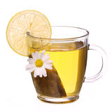 Cup of chamomile tea with chamomile flower, tea bag and lemon Stock Photography