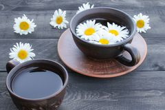Cup of chamomile tea and chamomile flowers on wooden background. Close-up stock image