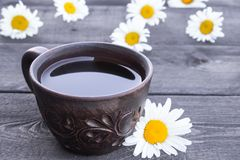 Cup of chamomile tea and chamomile flowers on wooden background. Close-up stock photo