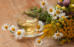 A cup of chamomile tea in a glass cup and a bouquet of field summer flowers on a wooden surface  Stock Photos