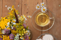 A cup of chamomile tea in a glass cup, bowl of marshmallows and a bouquet of field summer flowers on a wooden surface Stock Images