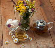 A cup of chamomile tea in a glass cup, bowl of marshmallows and a bouquet of field summer flowers on a wooden surface Royalty Free Stock Image