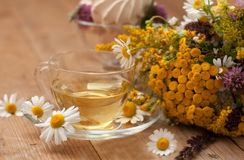 A cup of chamomile tea in a glass cup, bowl of marshmallows and a bouquet of field summer flowers on a wooden surface Royalty Free Stock Photos