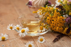 A cup of chamomile tea in a glass cup, bowl of marshmallows and a bouquet of field summer flowers on a wooden surface Stock Image