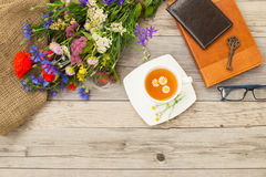 Cup of chamomile tea, purse, vintage key and bouquet of summer field flowers. Royalty Free Stock Photo