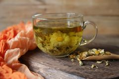Cup of chamomile tea with chamomile in spoon on rustic wooden background royalty free stock photos