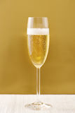 Cup of champagne on golden background Stock Image
