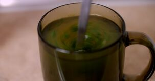 Cup of chicken broth with herbs mixing stock video