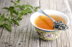 Cup of chinese tea on a wooden background with mint Stock Image
