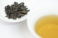 Cup chinesischer Tee mit den trockenen Teeblättern getrennt auf weißem Hintergrund Lizenzfreie Stockbilder