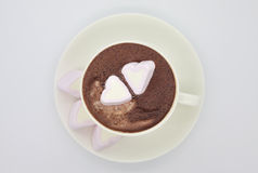 Cup of chocolate with heart shaped marshmallows. Cup of hot chocolate with delicious shugared heart shaped marshmallows. High key picture, white background. View Stock Photography
