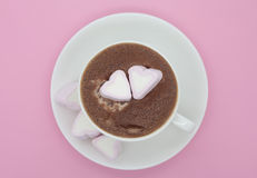 Cup of chocolate with heart shaped marshmallows. Cup of hot chocolate with delicious shugared heart shaped marshmallows. Light pink background Royalty Free Stock Image