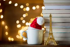 Cup with Christmas hat and Eiffel tower and books. White cup with Christmas hat and Eiffel tower and books or Fairy lights background Stock Image