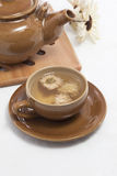 A cup of chrysanthemum tea and wood teapot pad Stock Image