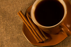 Cup and cinnamon. Stand on the table cover with sacking Royalty Free Stock Images