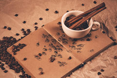 Cup with cinnamon sticks on drawing book Stock Photo