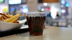 A cup of coca cola and fries on table at food court stock video footage
