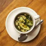 Cup of Coca Tea on Wooden table with Diagonal Lines, Peru, South America Royalty Free Stock Images