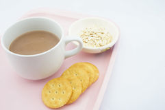 Cup of coco, oats and cracker. Cup of coco, oats in a small bowl and cracker placed on pink tray with white background Royalty Free Stock Image