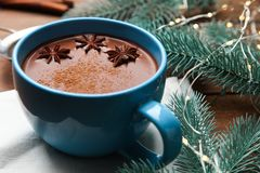 Cup of cocoa with badian. And christmas tree on wooden background. Concept winter drink stock photo