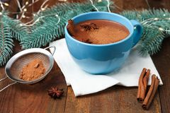Cup of cocoa with badian. And christmas tree on wooden background. Concept winter drink royalty free stock photos