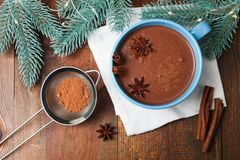 Cup of cocoa with badian. And christmas tree on wooden background. Concept winter drink. Top view royalty free stock photos