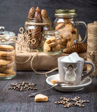 Cup of cocoa on a gray background. Cookies in glass jars Royalty Free Stock Photos