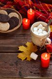 Cup of cocoa with marshmallow, chocolate cookie and peanut biscuit, book, blanket. Autumn relaxation, country lifestyle, seasonal Royalty Free Stock Photo