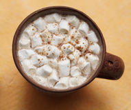 Cup of cocoa with marshmallow. Cocoa with marshmallow and cinnamon in a clay cup royalty free stock photography