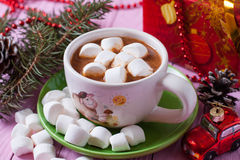 A cup of cocoa with marshmallows on pink background. On a wooden board Stock Photo