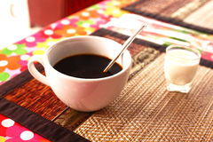 Cup of cofe and cream on bamboo mat Royalty Free Stock Photos