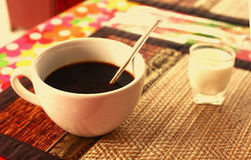 Cup of cofe and cream on bamboo mat Royalty Free Stock Images