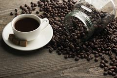Cup of cofee with sugar. Cup of cofee on the table next to jar filled with cofee beans stock image