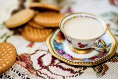 Cup of cofeee with cookies. Vintage elegant gilded cup of coffe with milk and cookies on lace tablecloth Royalty Free Stock Photo