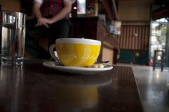 Cup of Coffe. Yellow cup of coffee server in coffee house Stock Images