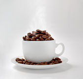 Cup and coffe beans. White cup filled with coffe beans Royalty Free Stock Photos