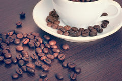Cup of coffe beans on a table Stock Photos