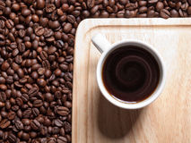 A cup of coffe. On breadboard with coffee grains stock image