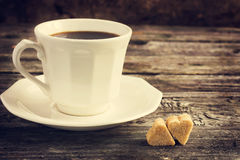 Cup of coffe and brown cane sugar with shape of heart on old woo Royalty Free Stock Photo