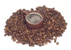Cup with coffe in coffee beans isolated onwhit Royalty Free Stock Photos